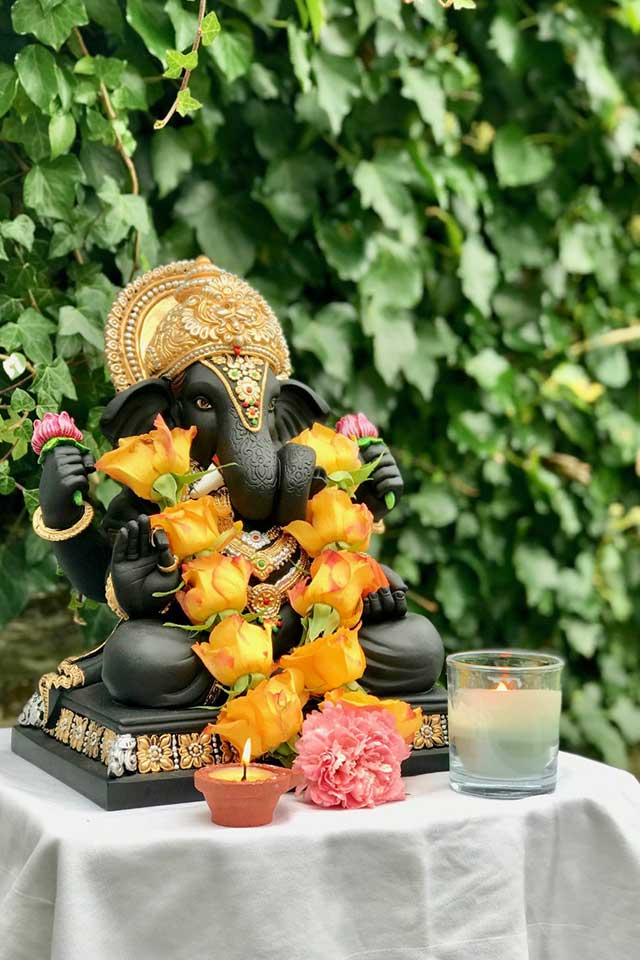 Ganesha statue with orange flowers and candles at Indian-Anglo fusion wedding