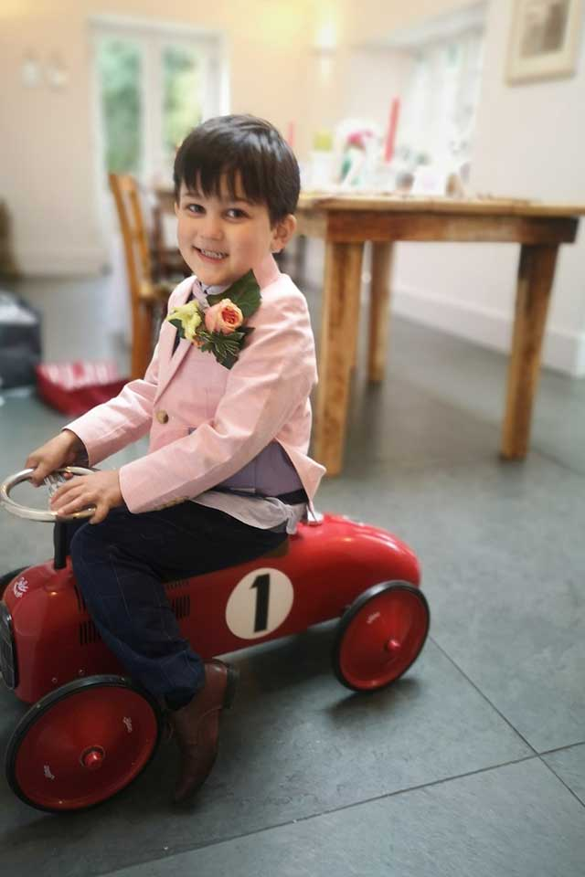 cute ringbearer riding red vintage car at small wedding