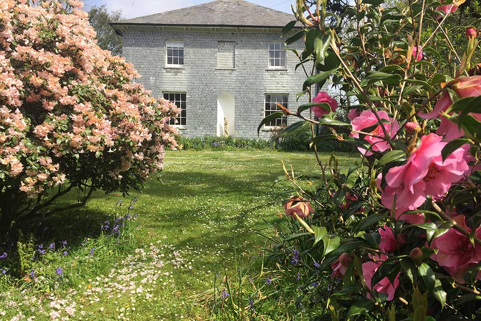 Treseren gardens with pink magnolia and green grass