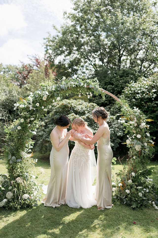 bridal party under floral moongate arch