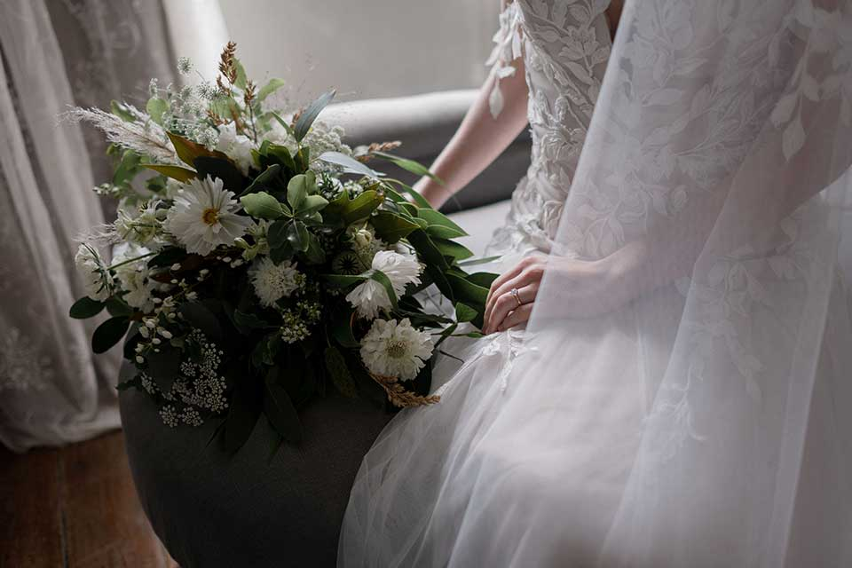 bride in bridal suite with white bouquet