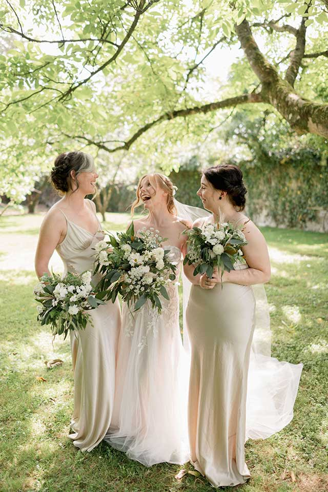 laughing bride with bridesmaids and bouquets