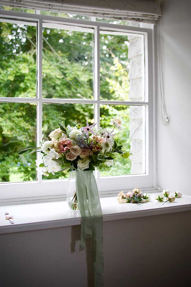delicate wedding bouquet on windowsill with ribbon