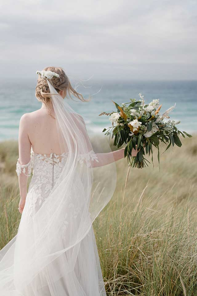 bride holding wedding flowers on the beach in Cornwall