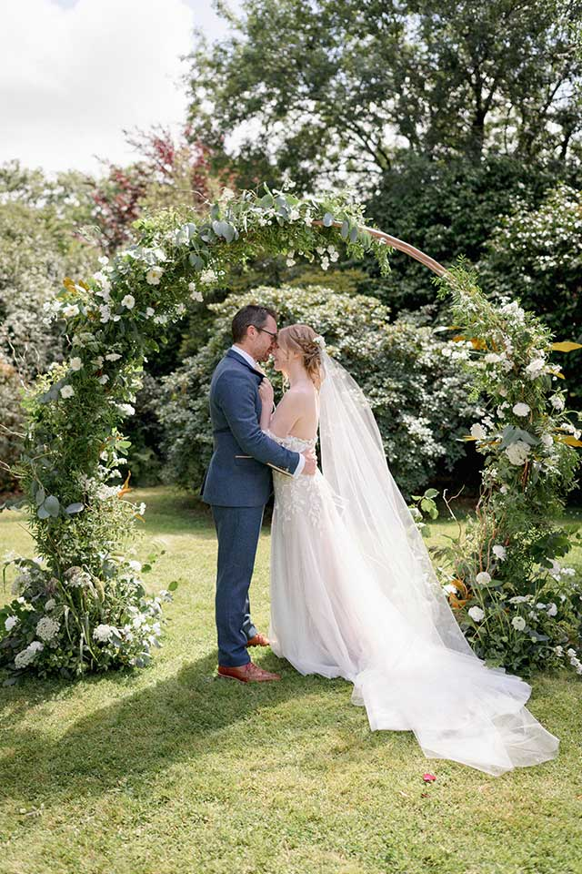 white and green floral arch wedding ceremony with bride and groom