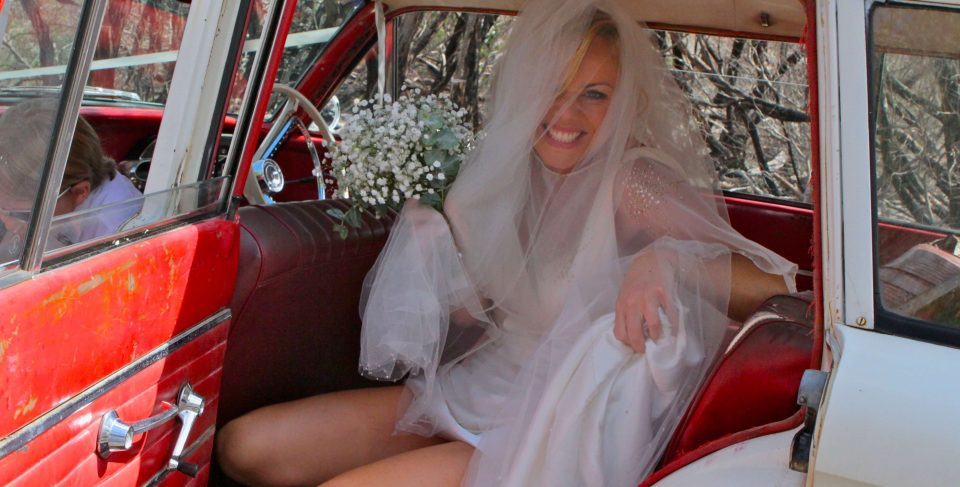 Bride arrives at wedding in vintage car door open showing vintage dress