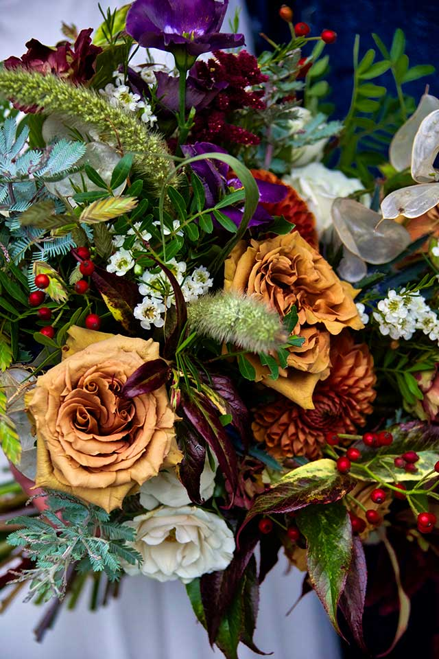 close up of autumn wedding flowers in deep orange, red and green