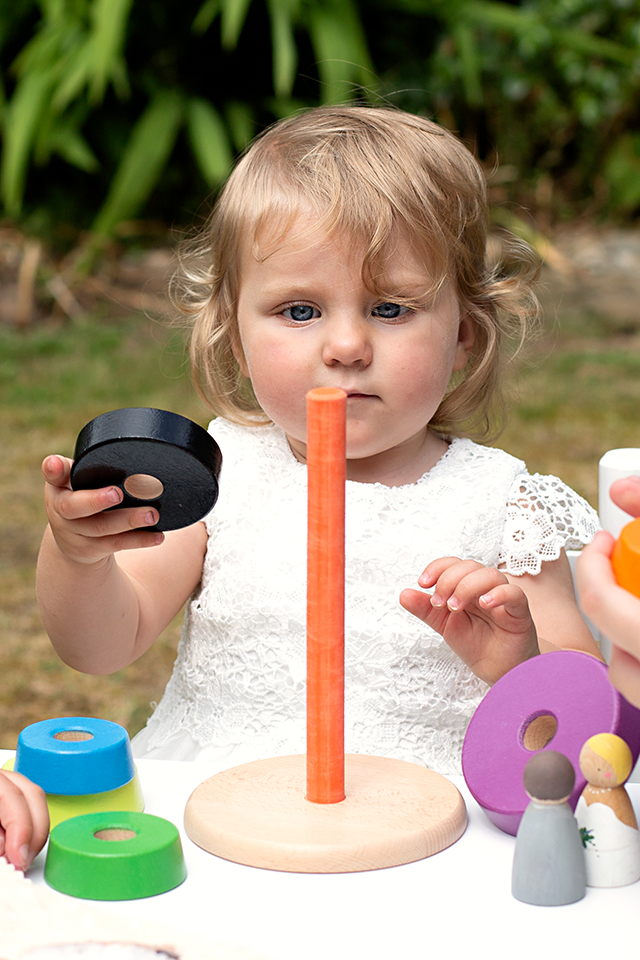 Small child playing with wooden toys at a small wedding
