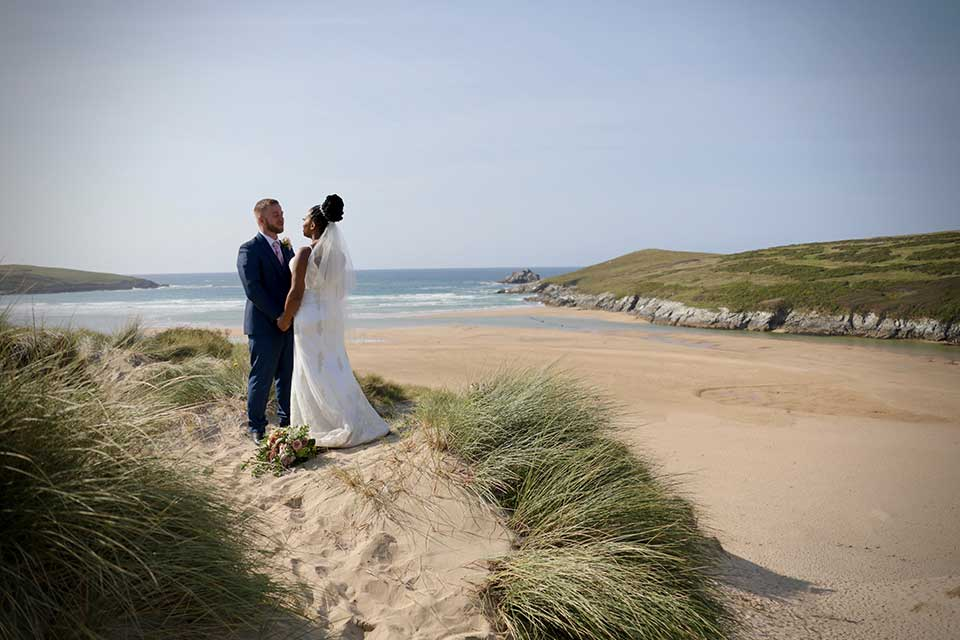 bride and groom on Holy well bay beach in Cornwall