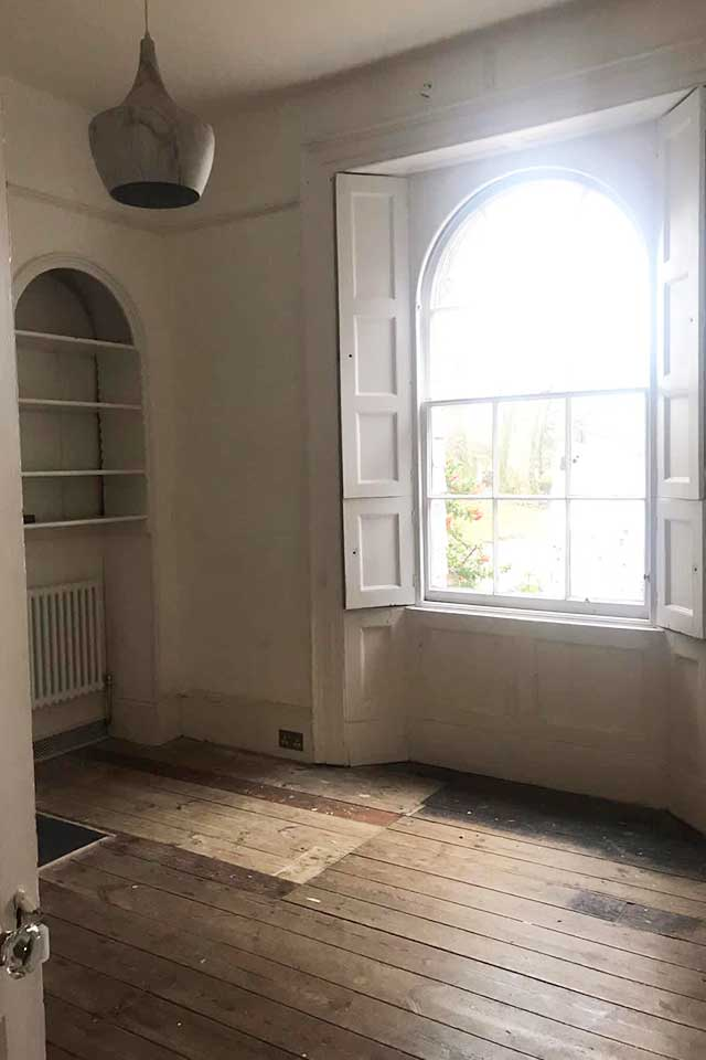 Room in Georgian house with stripped floorboards and white walls