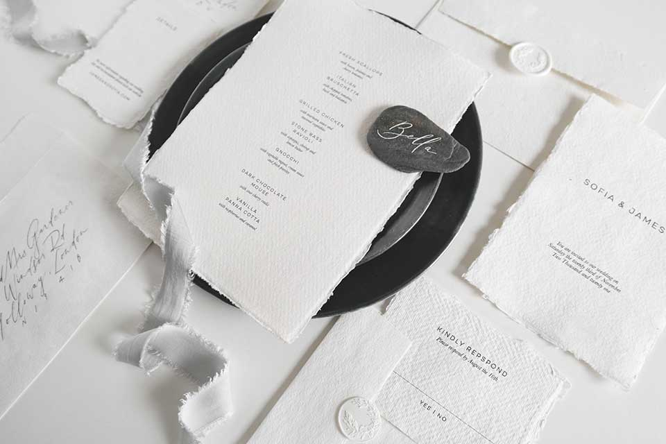 white wedding stationery with silk ribbon and torn edges