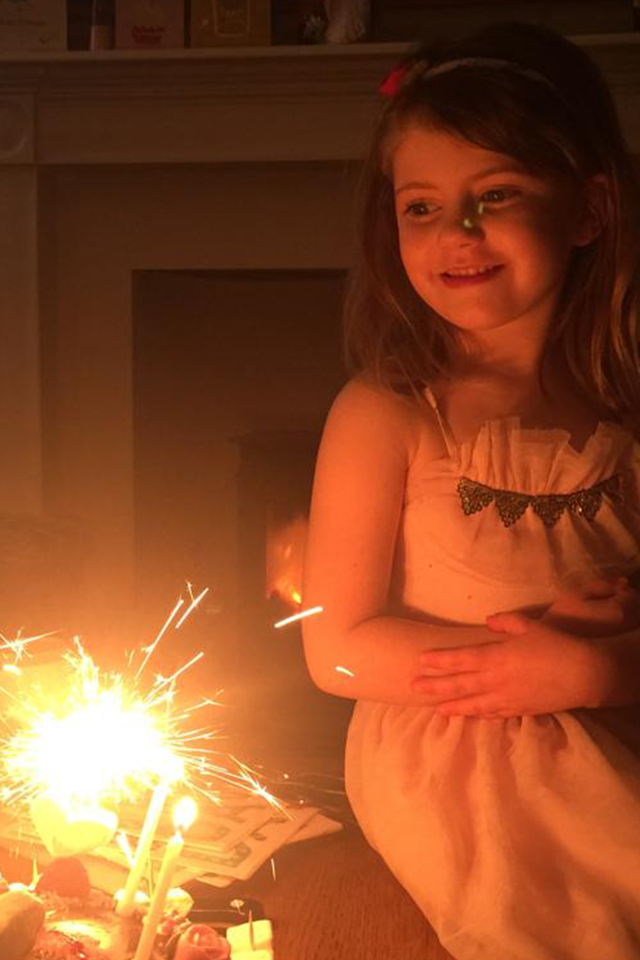 little girl with birthday cake candles