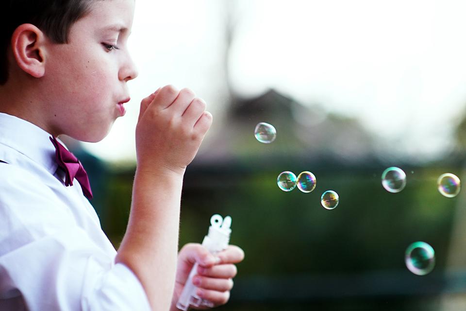 little boy blowing bubbles wedding