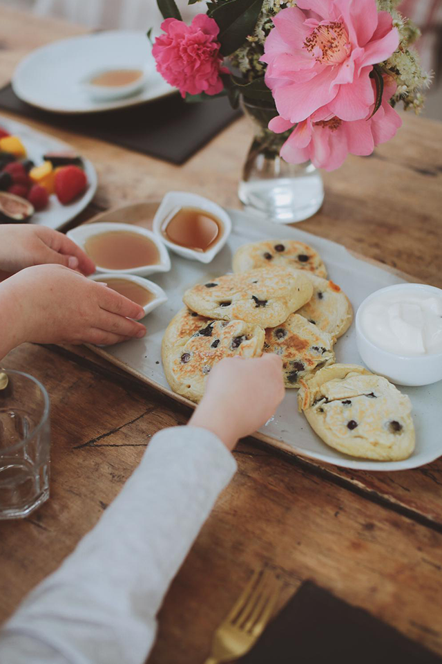 childs hand reaching for blueberry pancakes