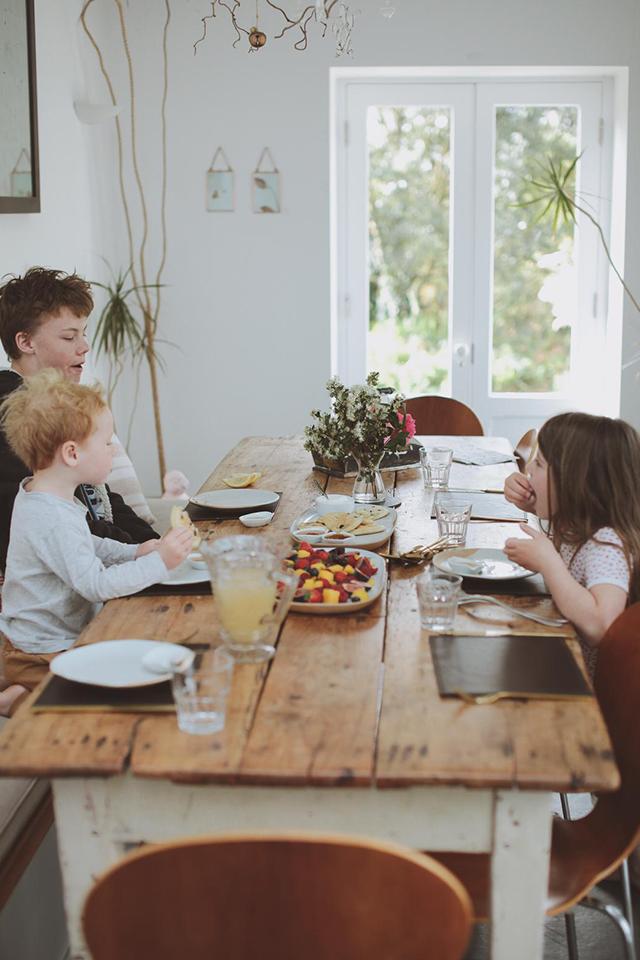 Children sat at breakfast table eating blueberry pancakes