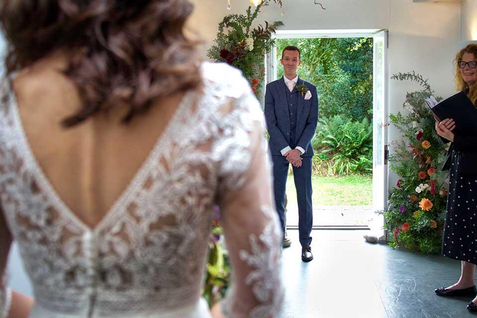 bride entering wedding ceremony with groom smiling
