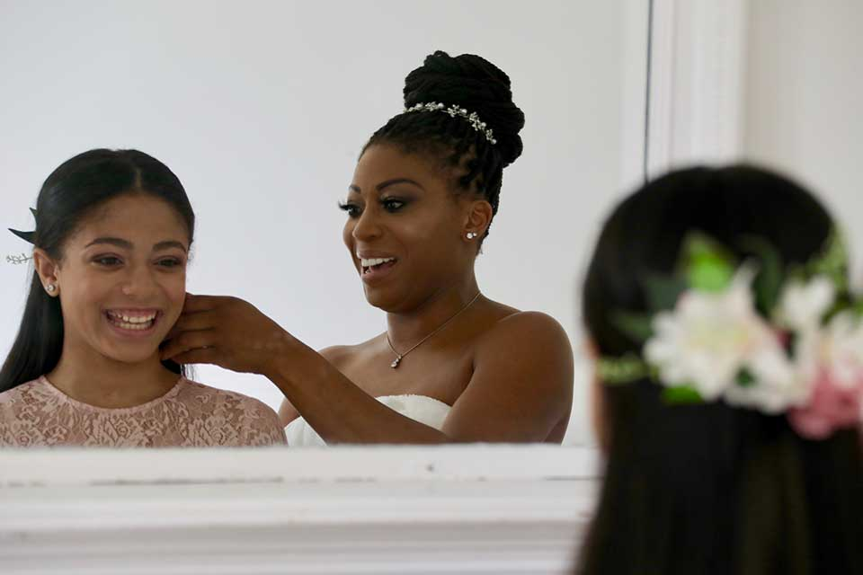 bride helping daughter do hair on wedding day