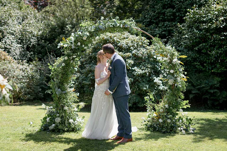 bride and groom kissing infront of moongate flower arch