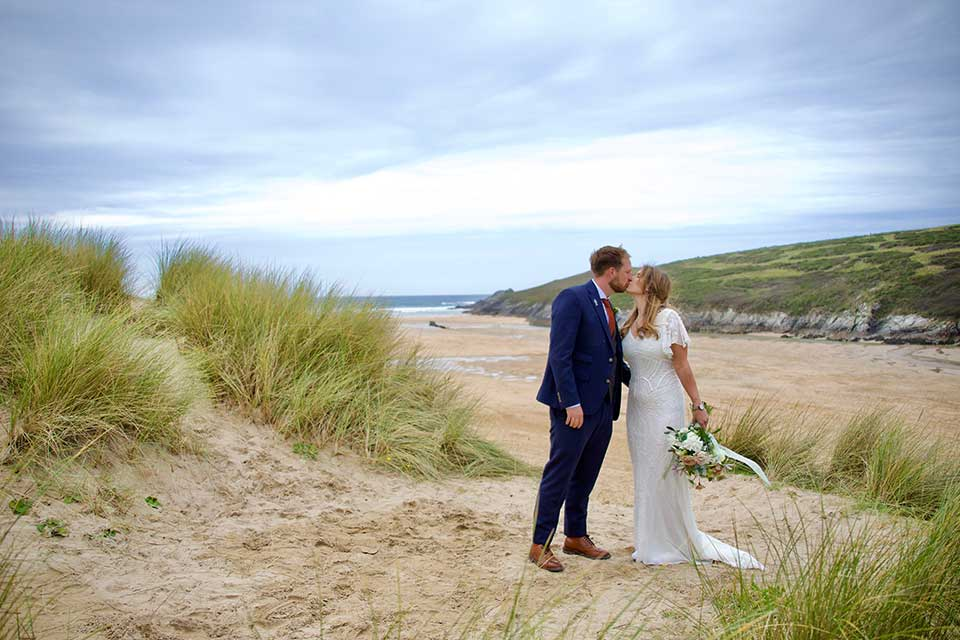 bride and groom kissing on the beach in Cornwall