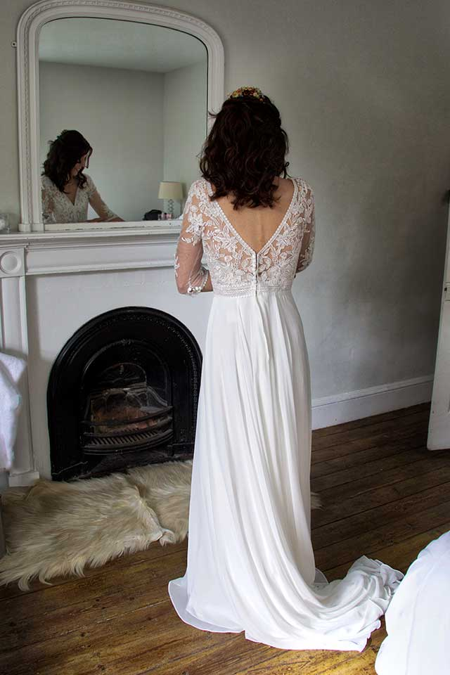 bride looking in the mirror wearing lace wedding dress