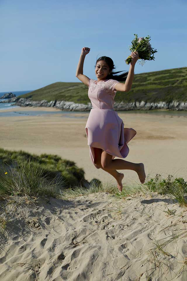 jumping happy bridesmaid on the beach