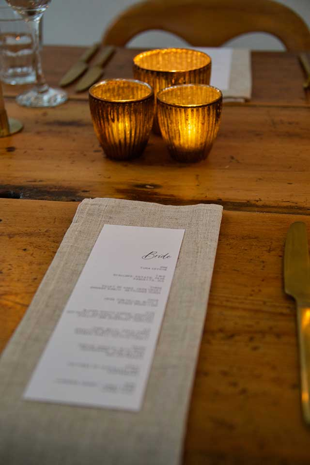 gold tealights and linen napkin with wedding menu on table