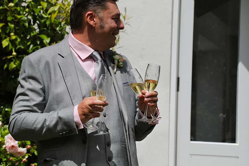 man in grey suit holding champagne glasses outside in sunshine