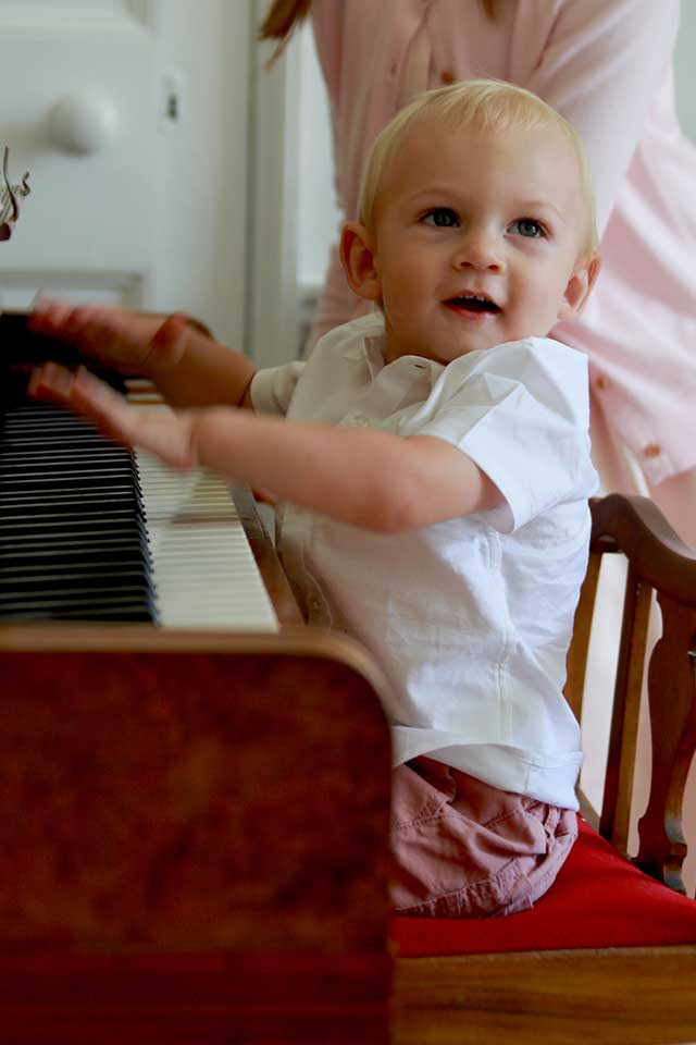 young boy playing Bechstein piano