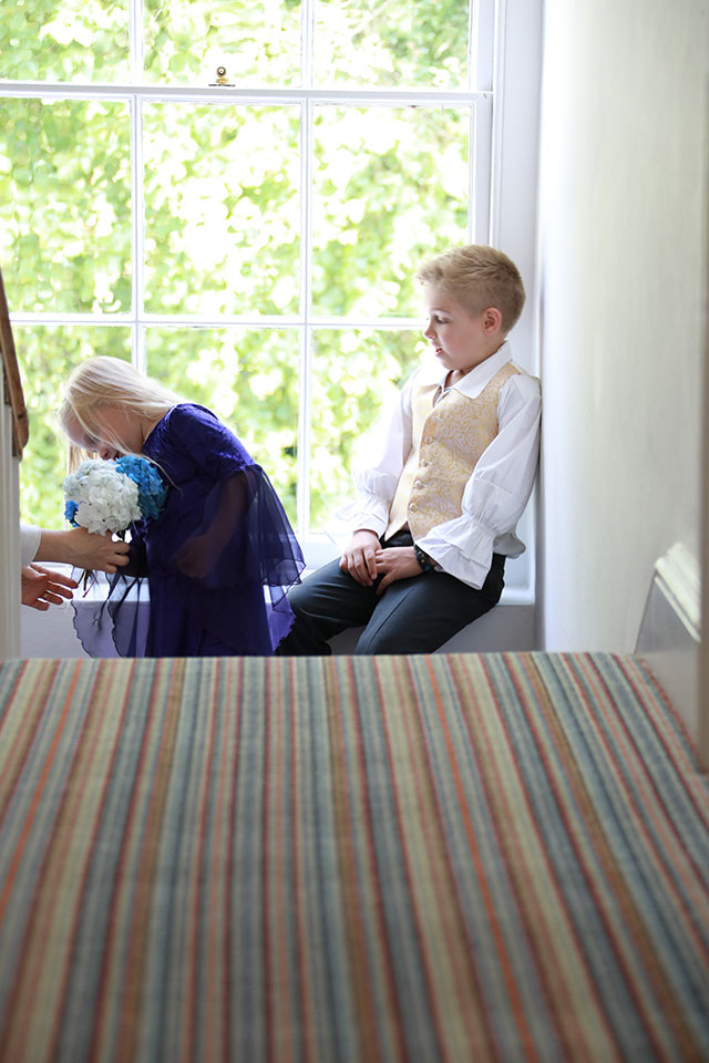 young boy and girl sitting in window in wedding clothes