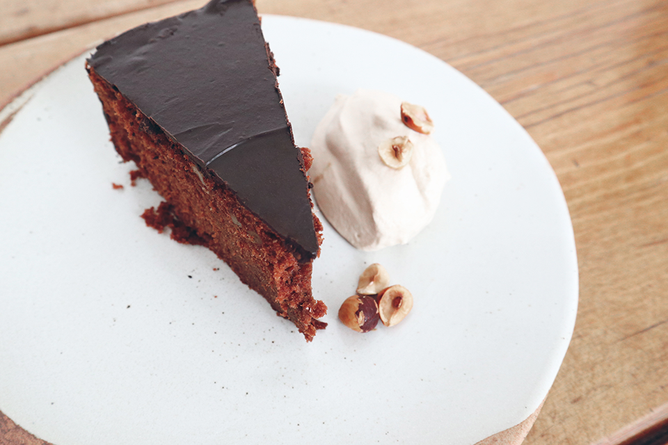 Slice of rich homemade chocolate cake on white plate
