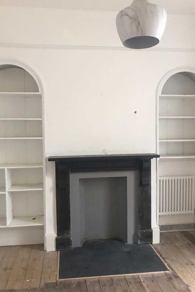 Empty white room with curved built in period shelves and fireplace
