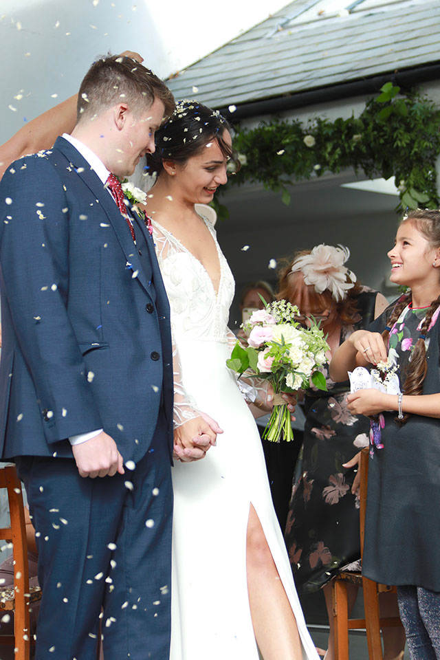 young girl throwing petal confetti at newly weds