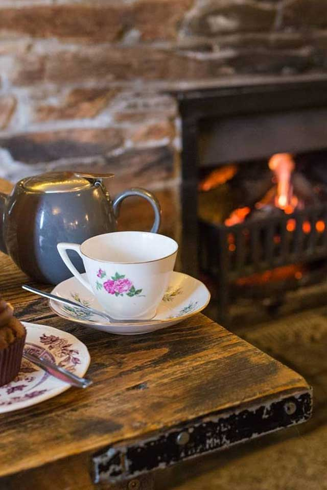 vintage teacup on wooden table in front of lit fire