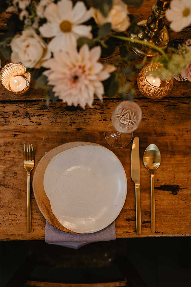 salt glazed plate and gold cutlery with flowers on wedding table