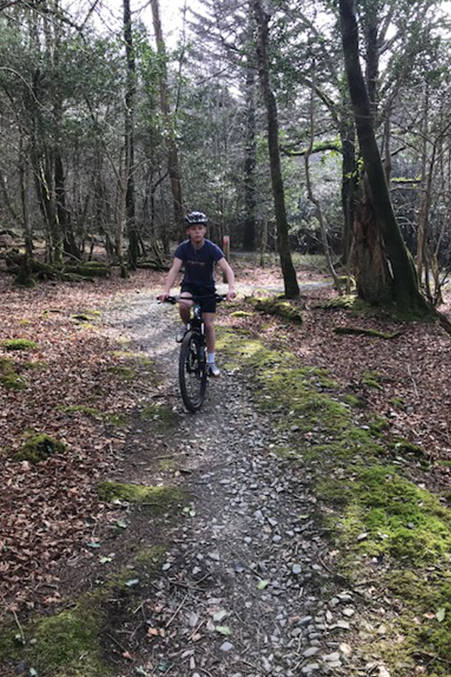 boy cycling bike trails woods