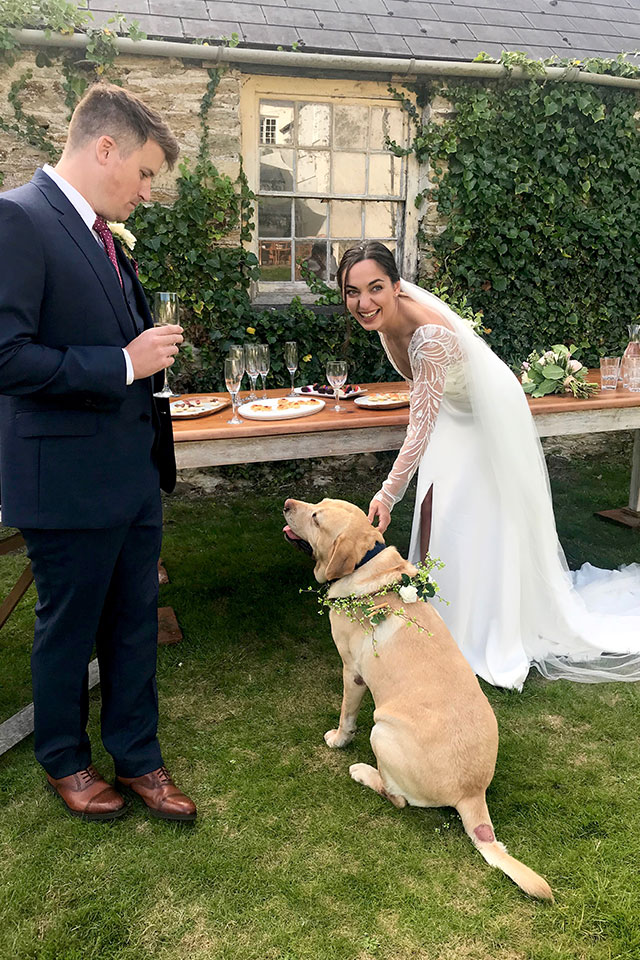bride and groom with family dog at wedding ceremony