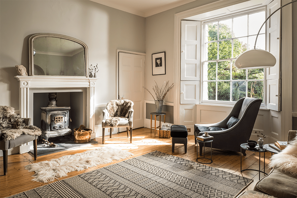 Georgian house drawing room with grey painted walls, large shuttered window with sun and fireplace