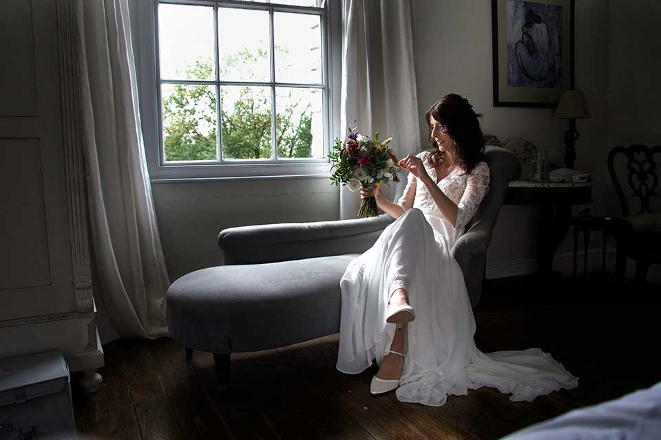 bride sat on grey chaise lounge in bridal suite