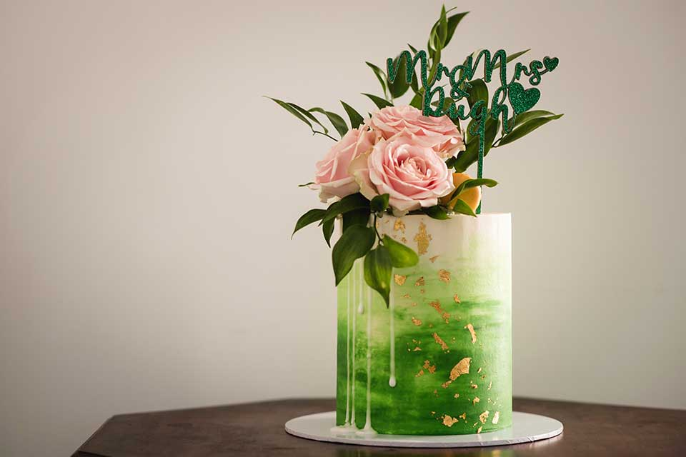 Emerald green buttercream small wedding cake with gold leaf and real pink roses