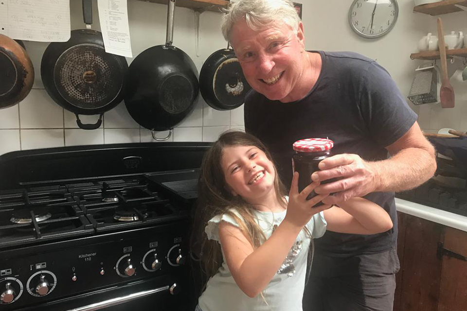 Girl and granddad with finished homemade jars of jam