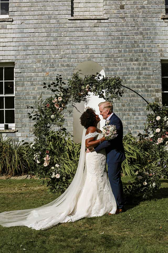 couple under floral arch on wedding day