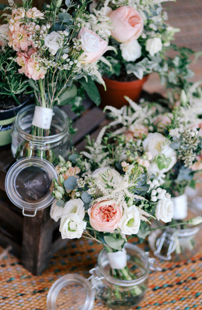 pink and cream wedding flowers in glass jars