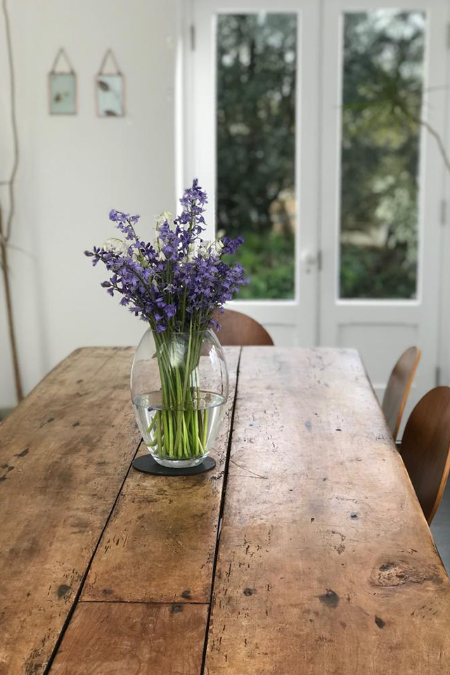 Cornish bluebells in large glass vase on wooden farmhouse table in front of patio doors