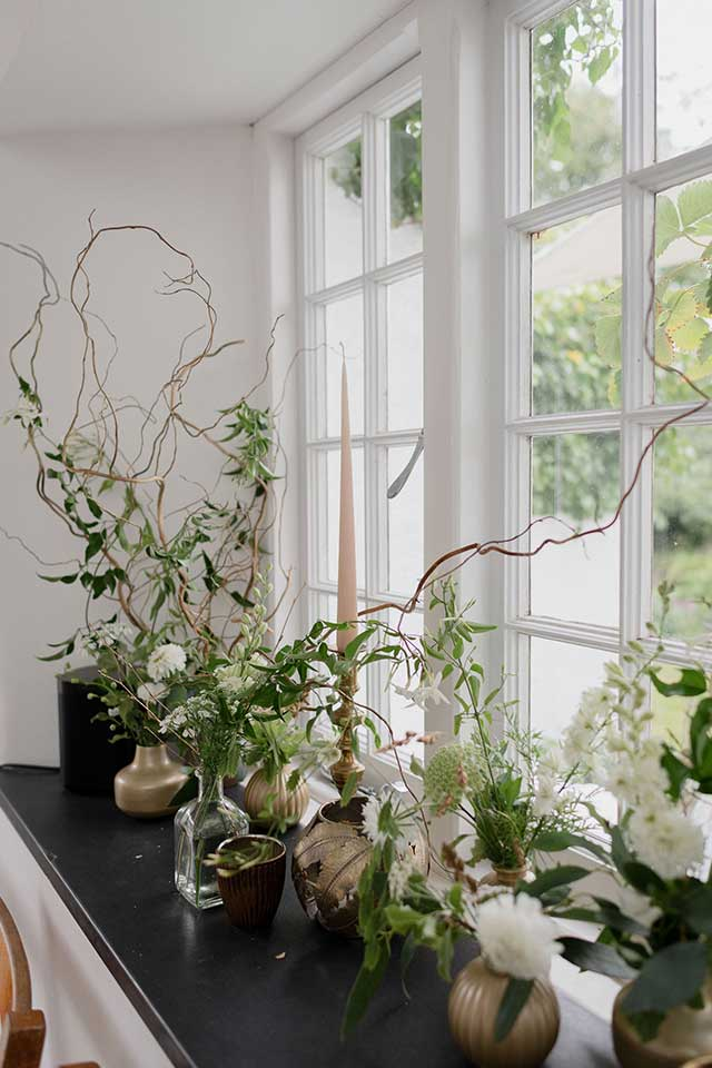 delicate vases on windowsill with flowers
