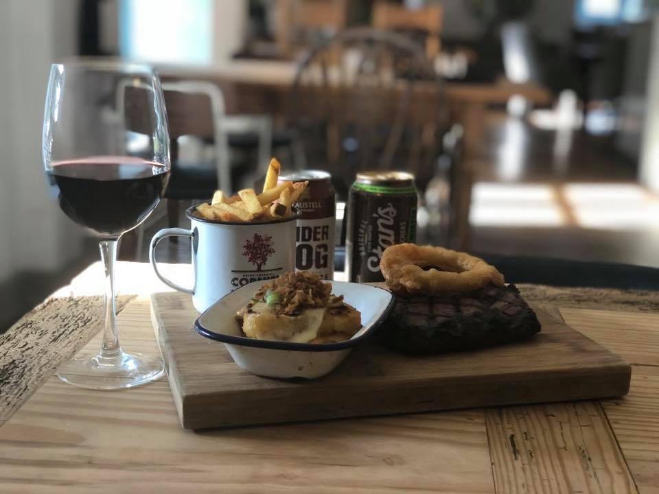 Pub food on brown board glass of red wine