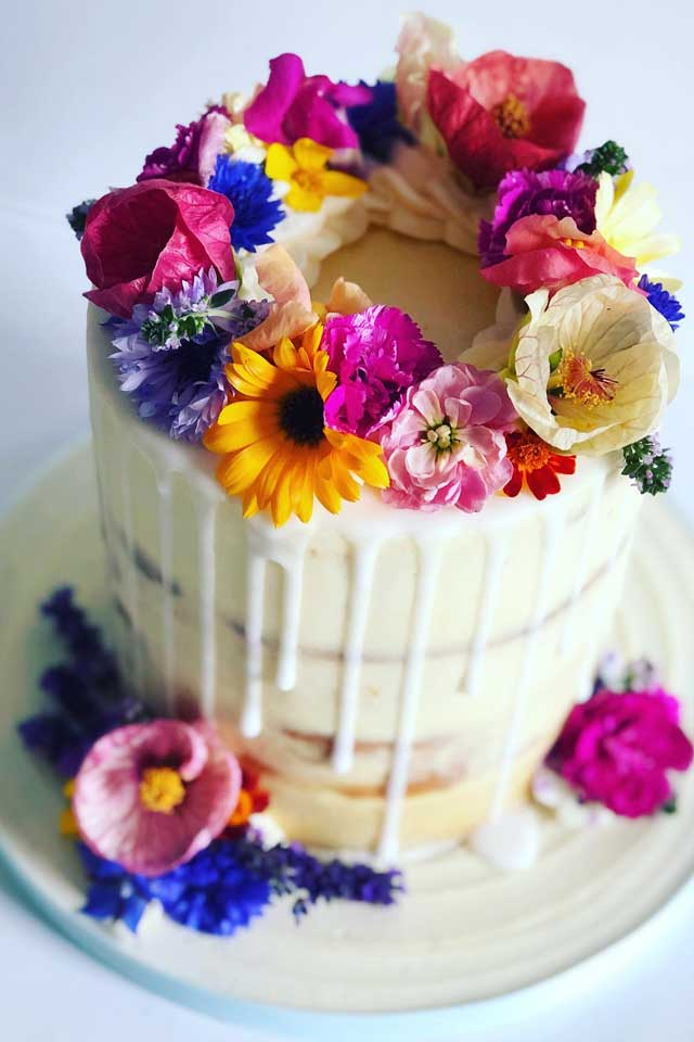 vibrant colours wedding cake with fresh flowers and drip