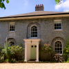 Front of Georgian country house in Cornwall with sage green door and white pillars.
