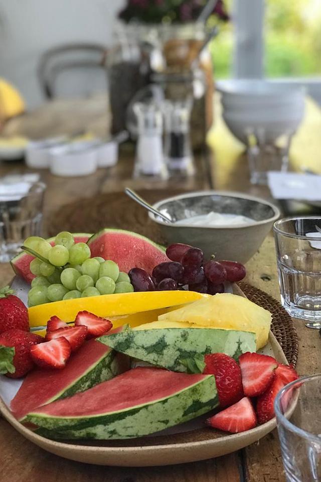 Fruit platter and bowl of greek yoghurt on breakfast table