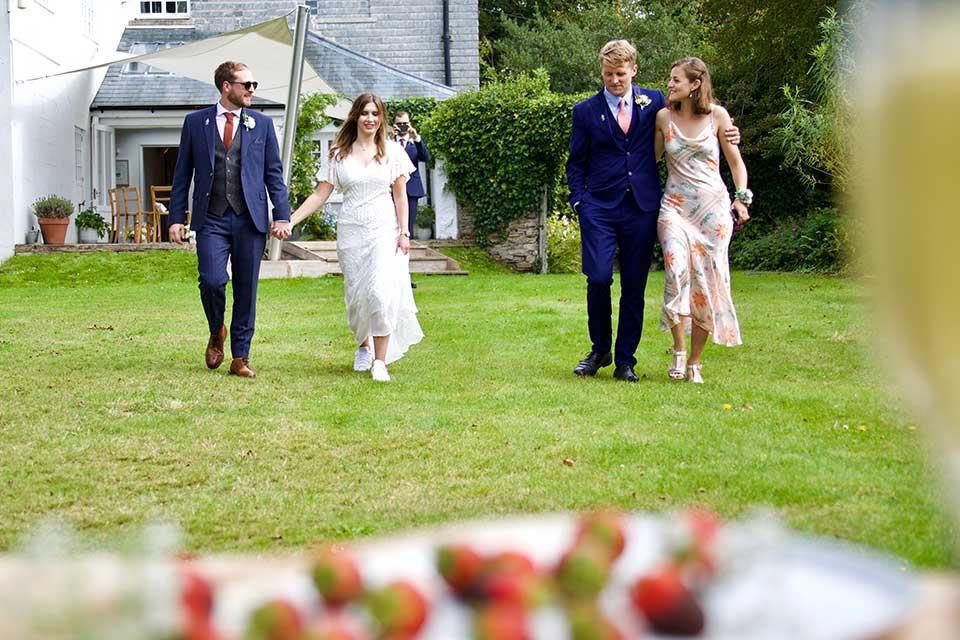 small wedding party walking across garden