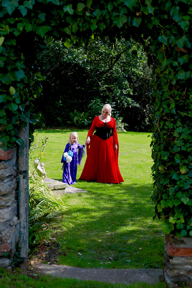 Bride in red wedding dress walking with young bridesmaid